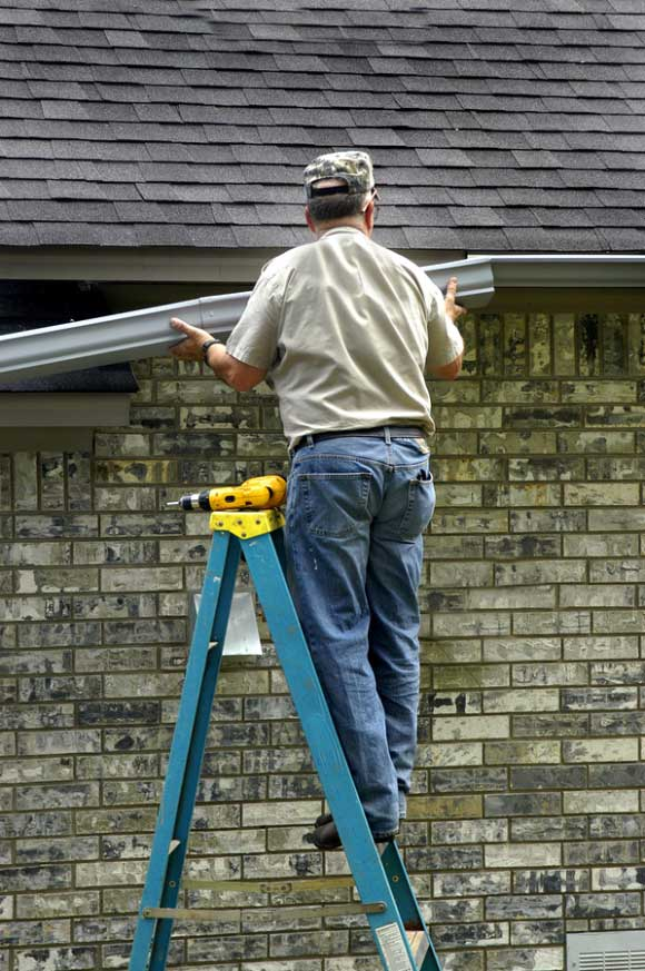 man fixing gutters