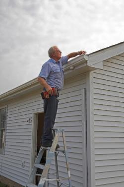 man repairs gutters